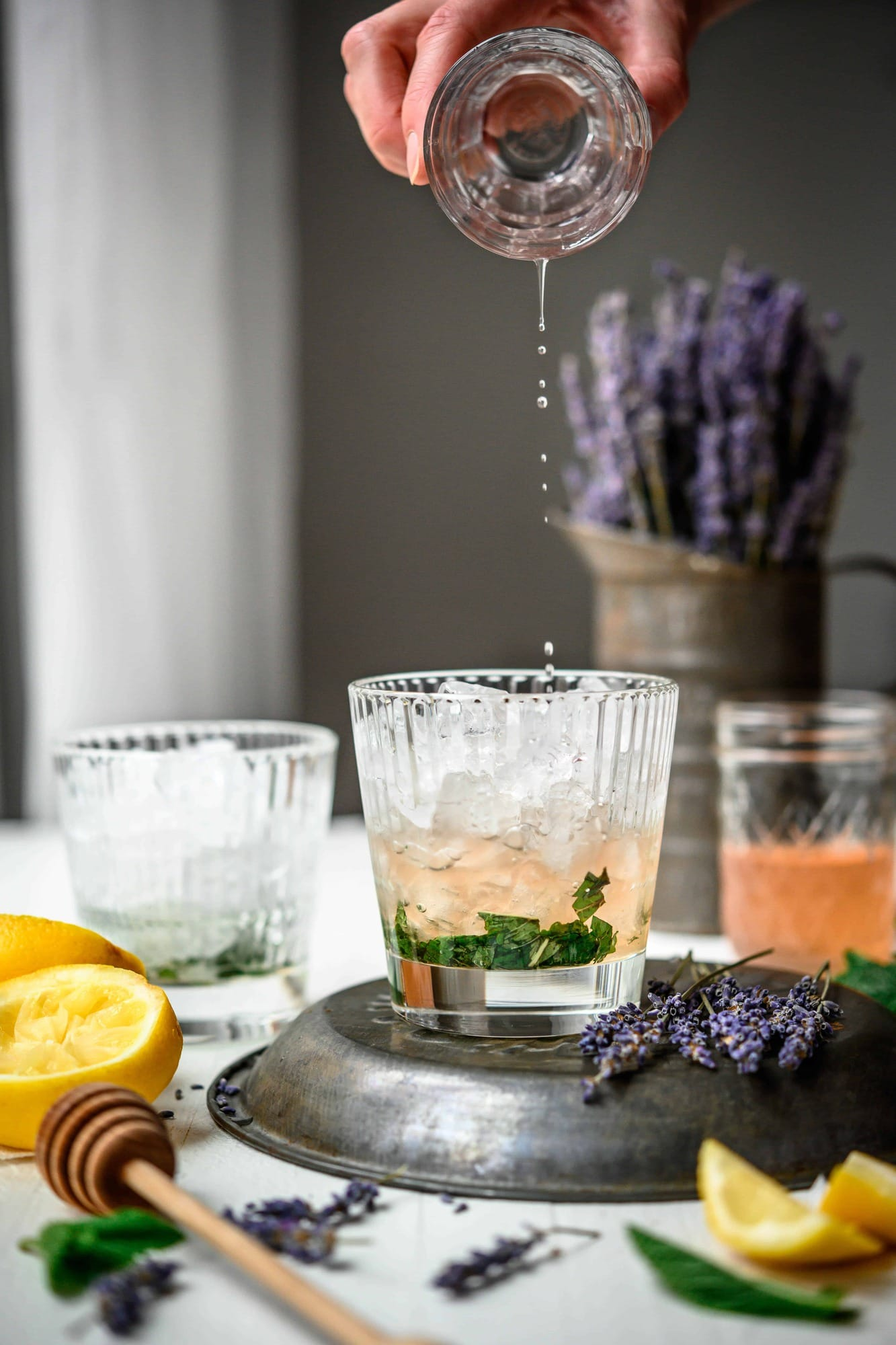 Side view of pouring homemade lemon lavender simple syrup over ice and muddled mint