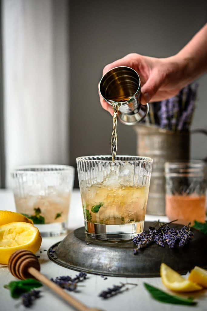 Side view of pouring bourbon into homemade mint julep