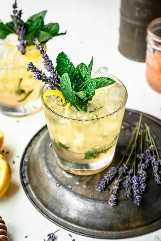 High side view of lemon lavender mint julep garnished with fresh mint, lavender and lemon peel