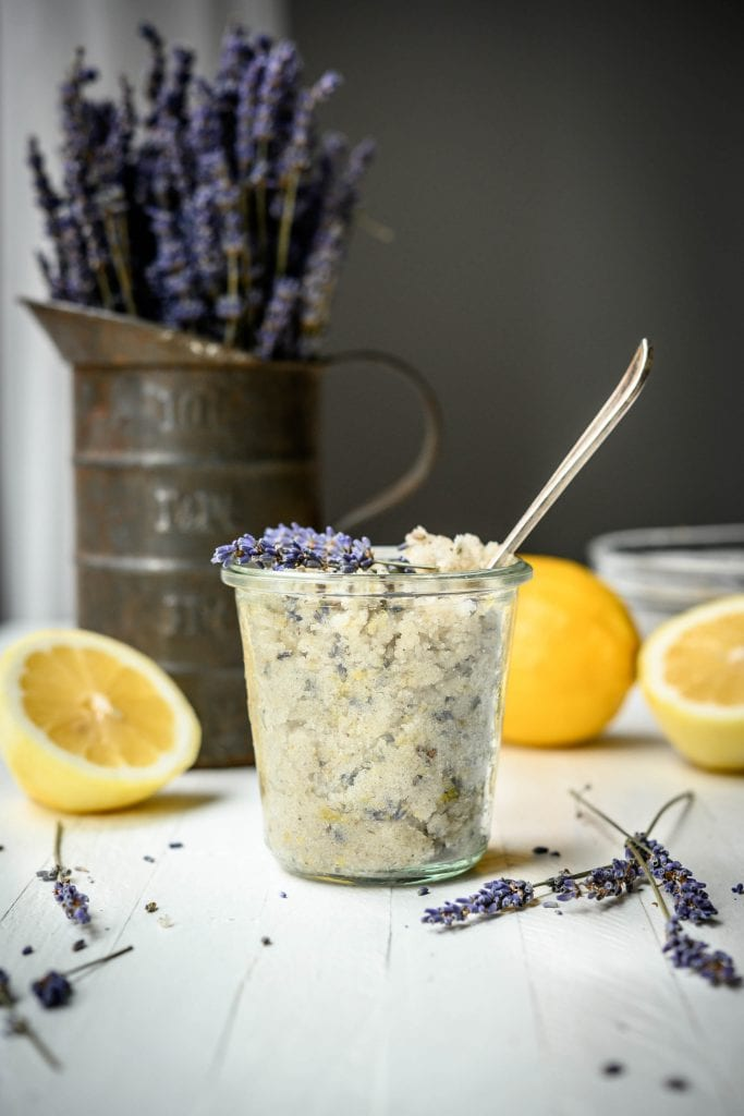Side view of lavender lemon sugar scrub in glass jar with dried lavender and lemons in background