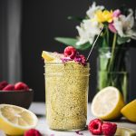 Side view of lemon turmeric chia pudding in a glass jar with fresh raspberries and flowers in background