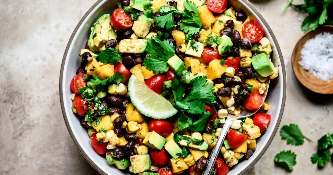 Overhead view of Grilled Corn, Black Bean & Avocado Salad in a white bowl on rustic background
