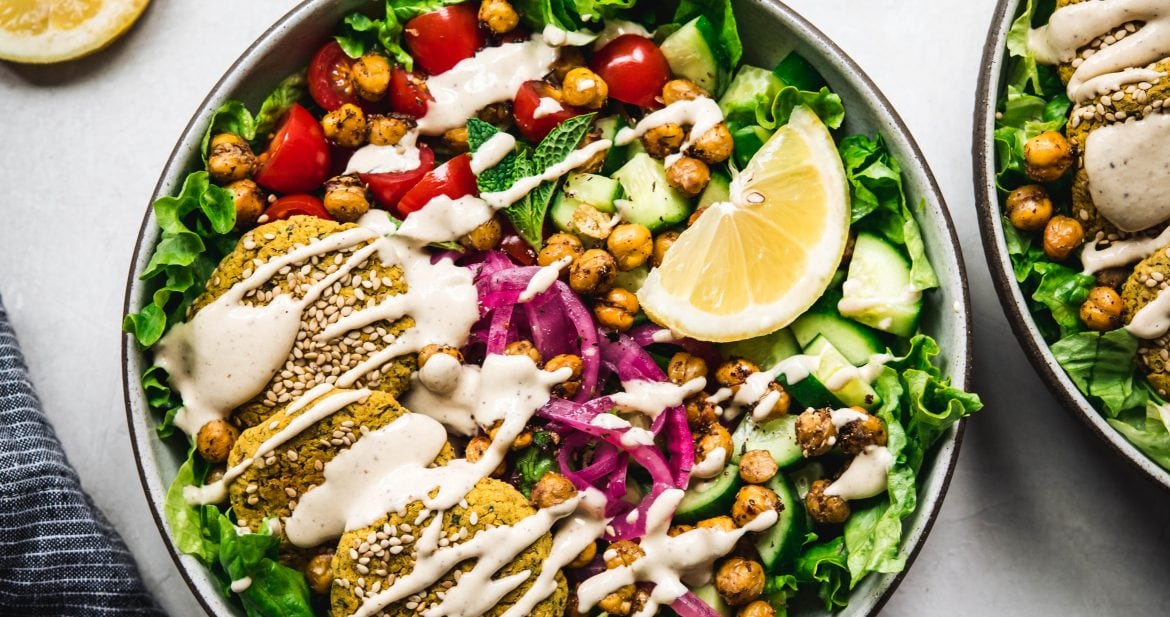 Overhead view of mediterranean salad with falafel and a tahini drizzle on white background