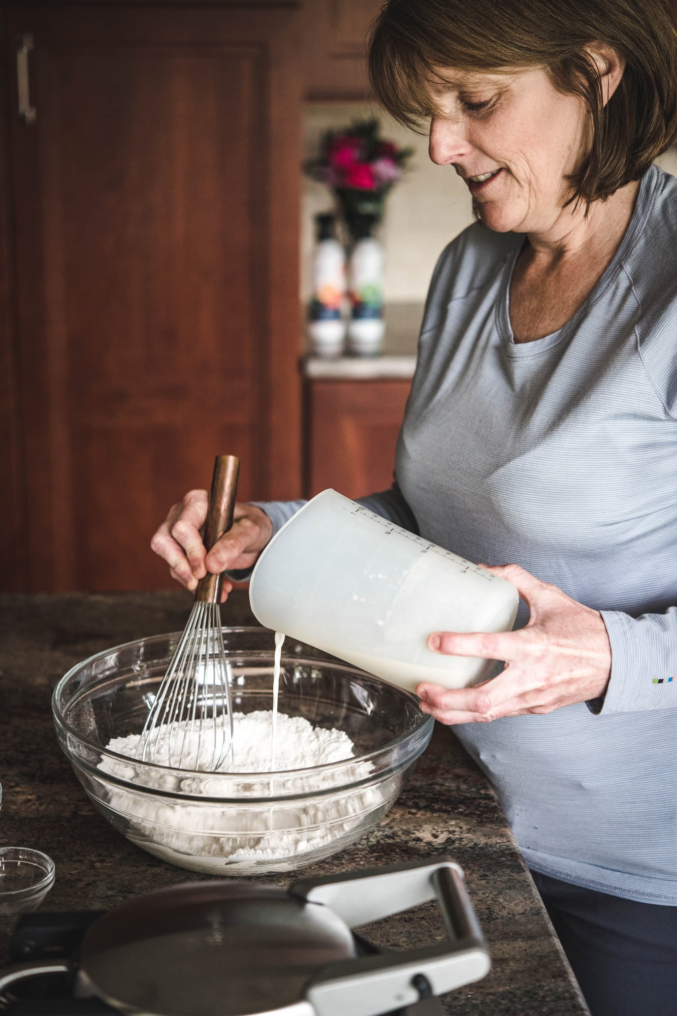 Woman pouring milk into waffle batter