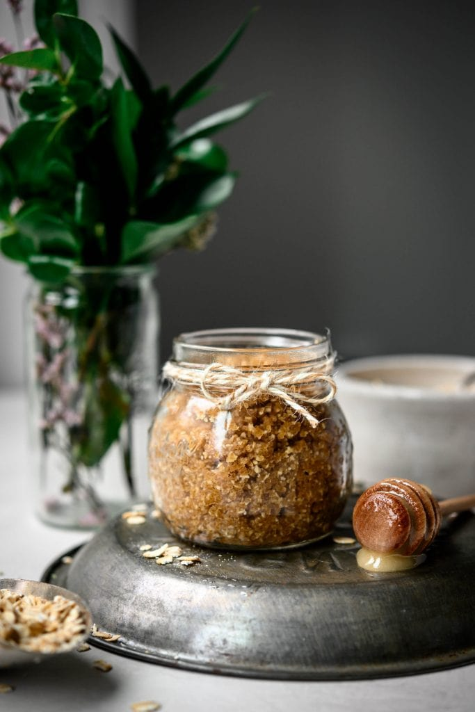 Side view of oatmeal cookie body scrub in a small glass jar with greenery in background