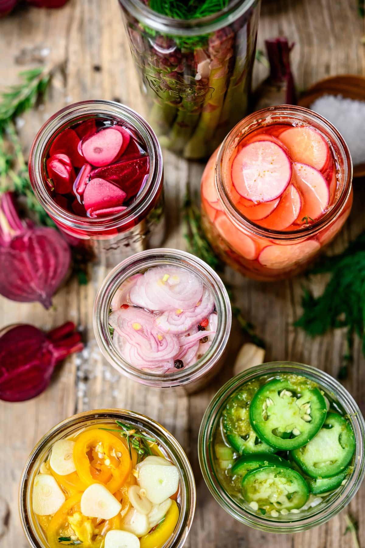 Overhead view of colorful pickled vegetables in glass jars on wood tables