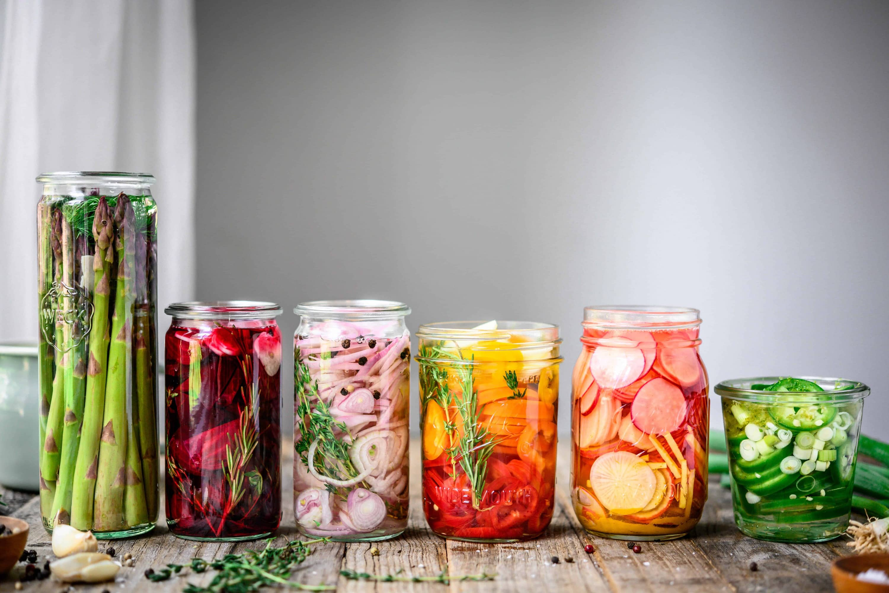 Side view of homemade rainbow quick pickles in glass jars on wood table