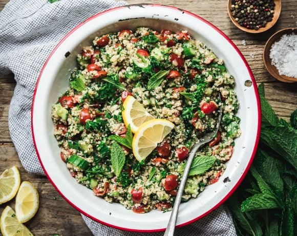 Overhead view of quinoa tabbouleh in a white and red enamel bowl on wood table