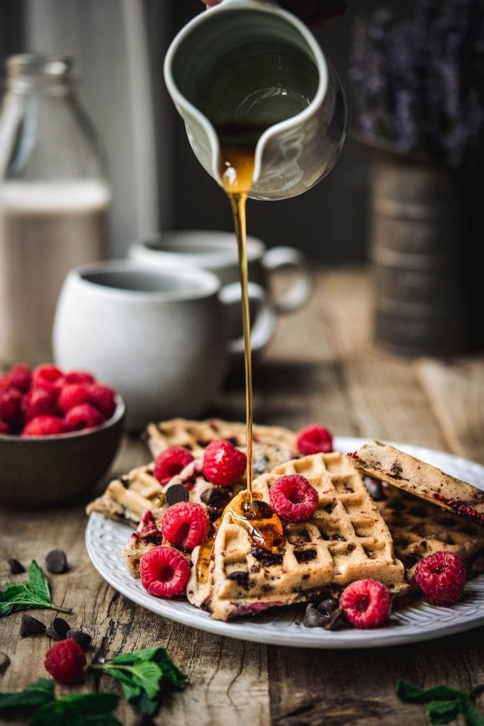 Pouring maple syrup onto raspberry chocolate chip waffles on white plate with fresh raspberries