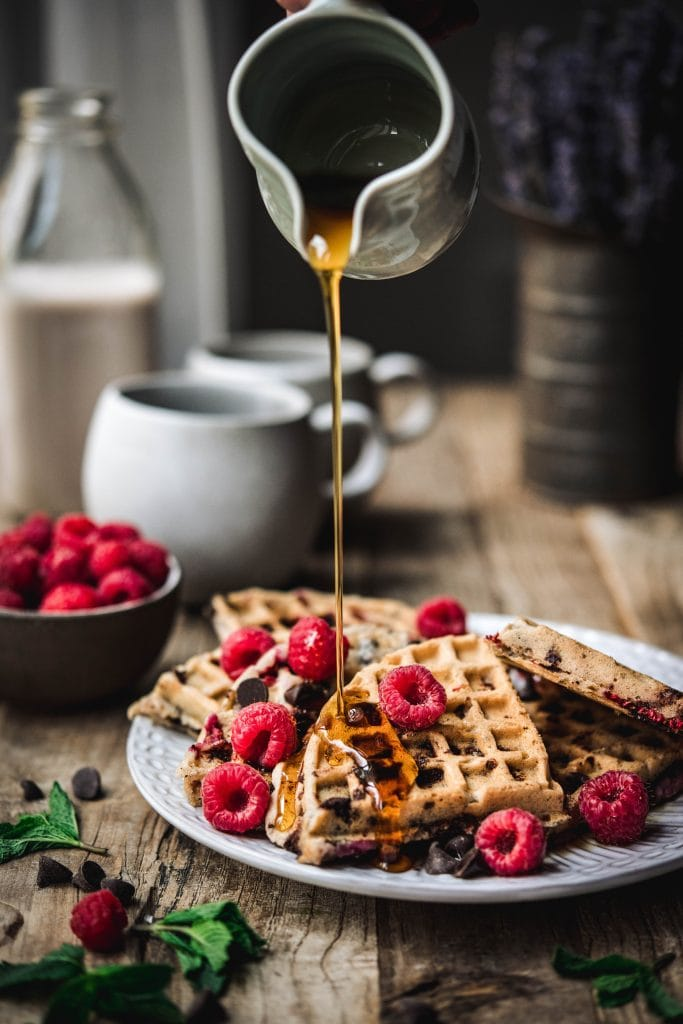 Pouring maple syrup onto raspberry chocolate chip waffles