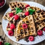 High side view of raspberry chocolate chip waffles with fresh raspberries and mint on white plate