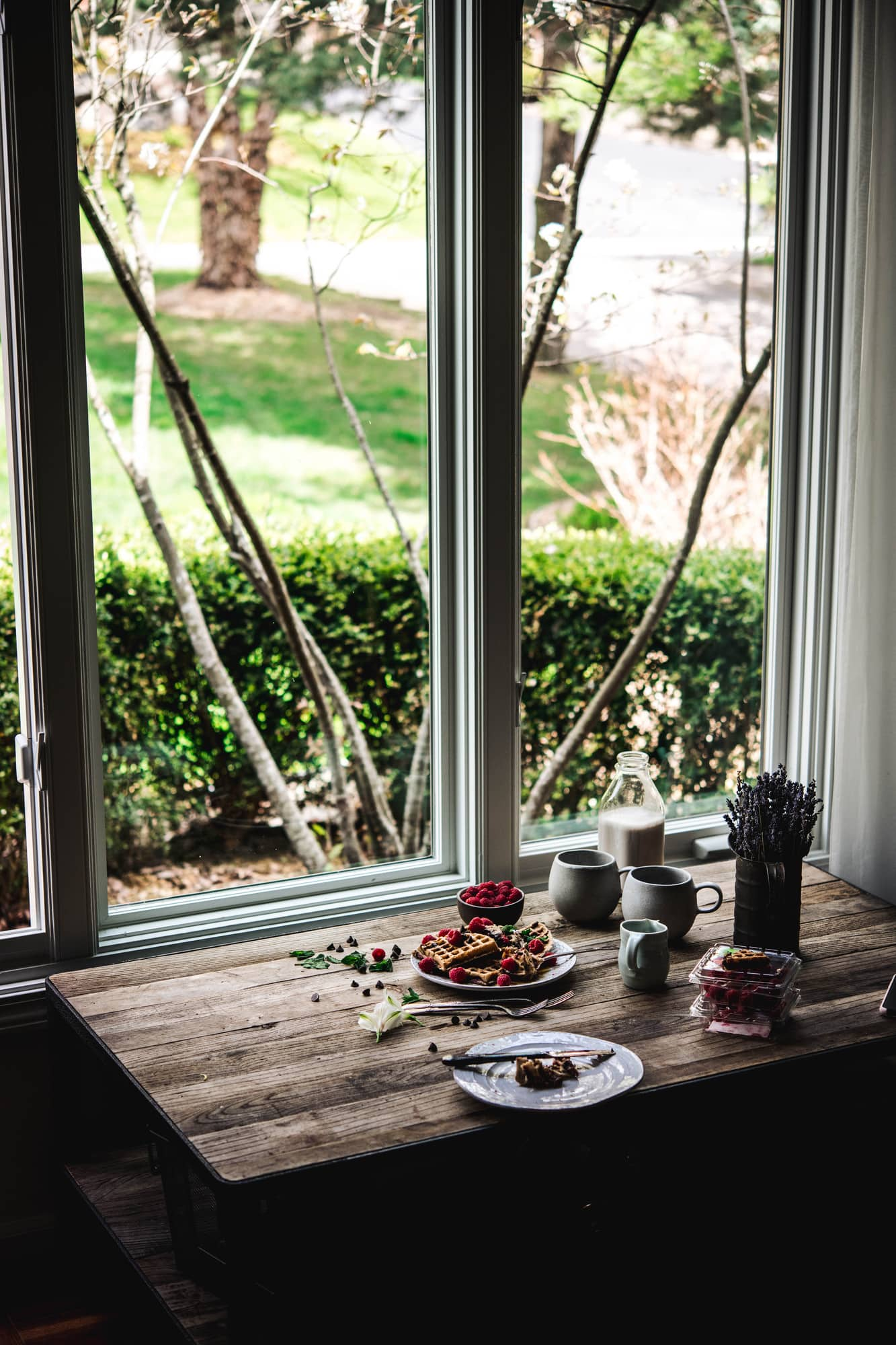 Side view of food photography setup with a wood table next to a large window