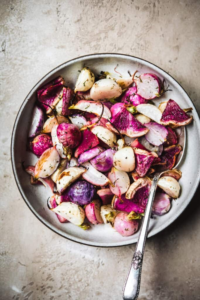 Close up overhead view of dill roasted radishes in a white bowl on a rustic brown background