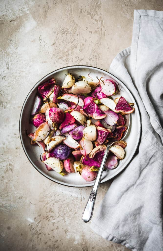 Overhead view of dill roasted radishes in a white bowl on a rustic brown background with grey towel