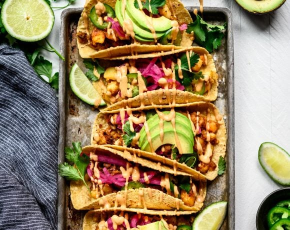 Overhead view of spicy breakfast potato tacos with avocado on a metal tray on white background