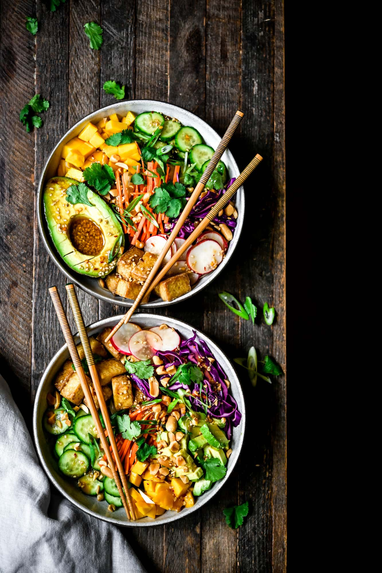 Overhead view of two bowls of vegan spring roll bowl with crispy tofu and avocado on wood background