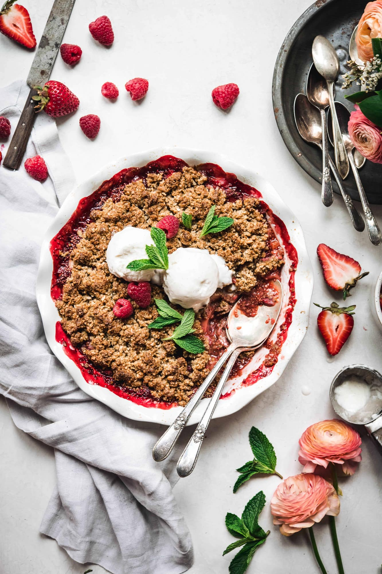 Overhead view of Vegan Strawberry Rhubarb Crumble topped with vanilla ice cream and mint on white background