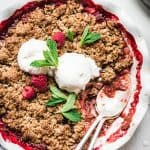 Close up overhead view of Vegan Strawberry Rhubarb Crumble topped with vanilla ice cream and mint on white background