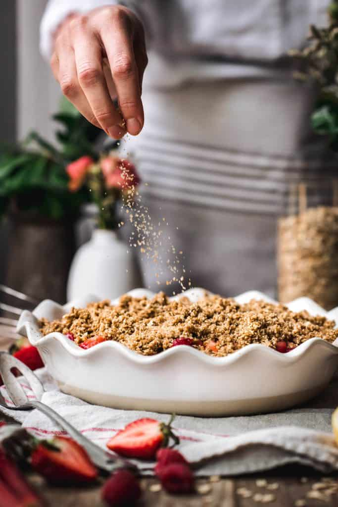 Beautiful food photography of sprinkling sugar on top of strawberry rhubarb crumble