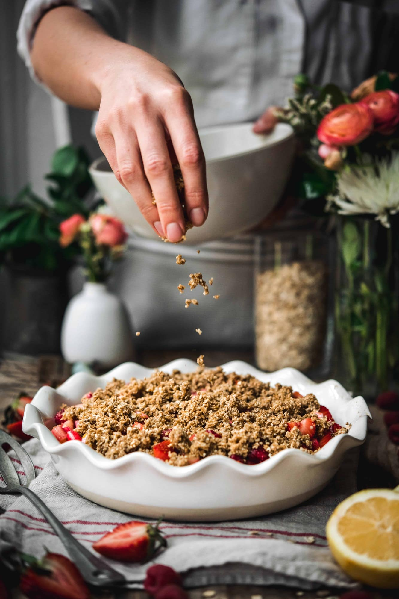 Person sprinkling crumble topping on top of strawberry rhubarb crisp with flowers in background