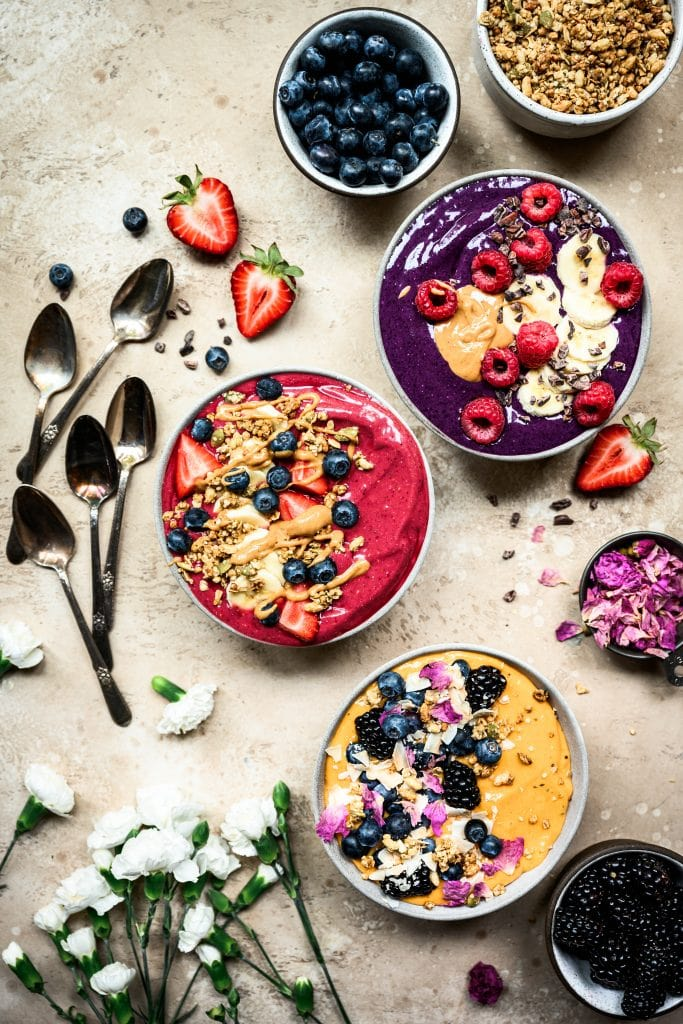Overhead view of 3 beautiful red, purple and yellow summer smoothies bowls on rustic brown surface
