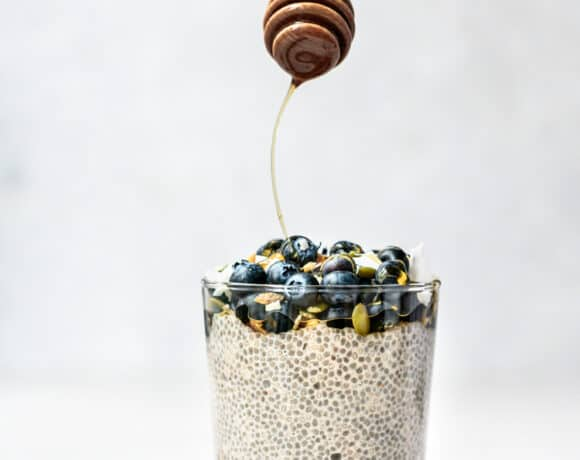 Side view of drizzling maple syrup onto vanilla chia pudding topped with blueberries