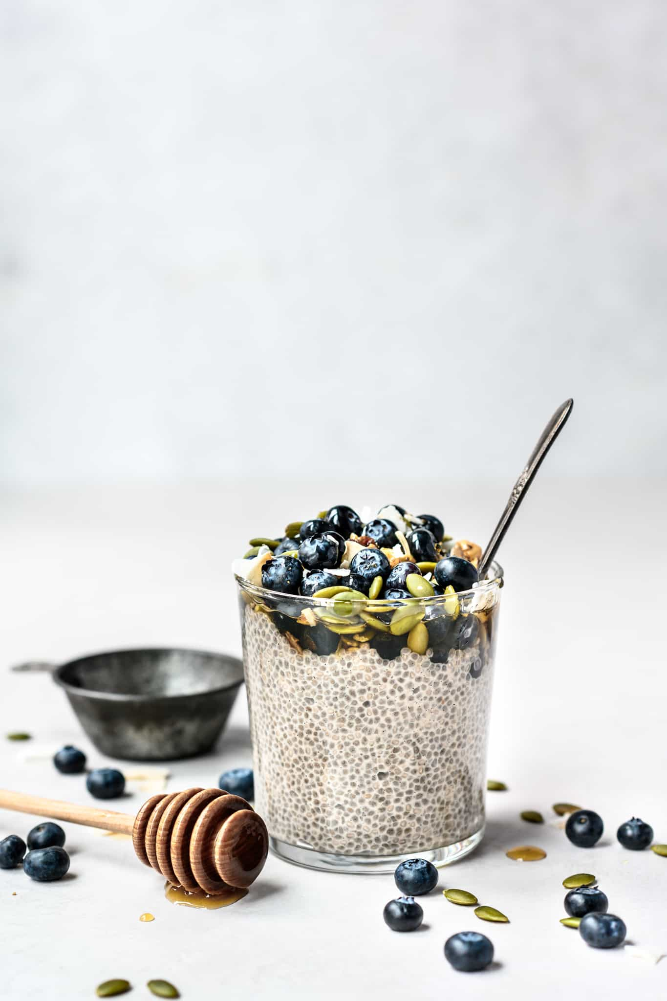 Side view of jar of maple vanilla chia pudding topped with blueberries and pepitas on white background
