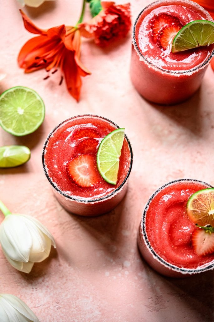 Overhead view of 3 frozen jalapeño watermelon margaritas on pink background