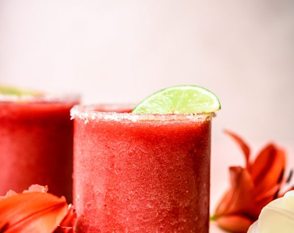 Side view of frozen jalapeño watermelon margaritas on pink background