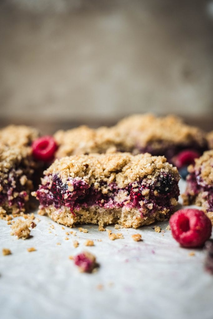Vegan, gluten free four berry pie bars with a bite taken out
