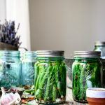 Side view of spicy pickled dilly beans in blue Ball jar
