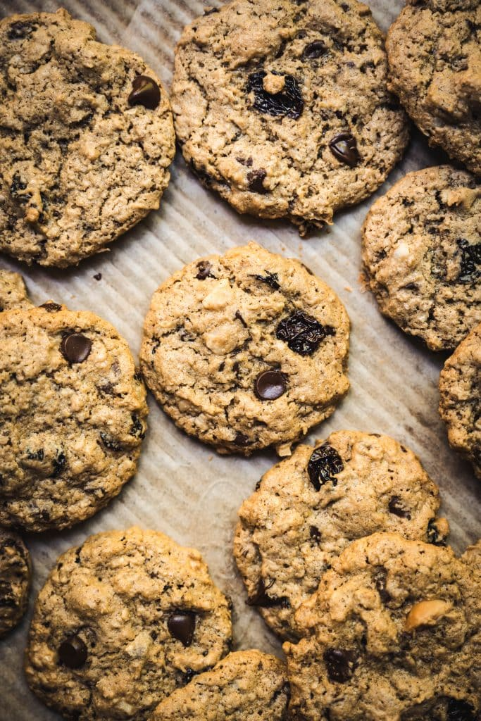 Overhead view of chocolate chip cherry cookies with macadamia nuts on parchment paper-lined tray