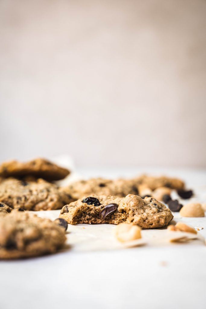 Side view of chocolate chip cherry cookies with macadamia nuts on white background