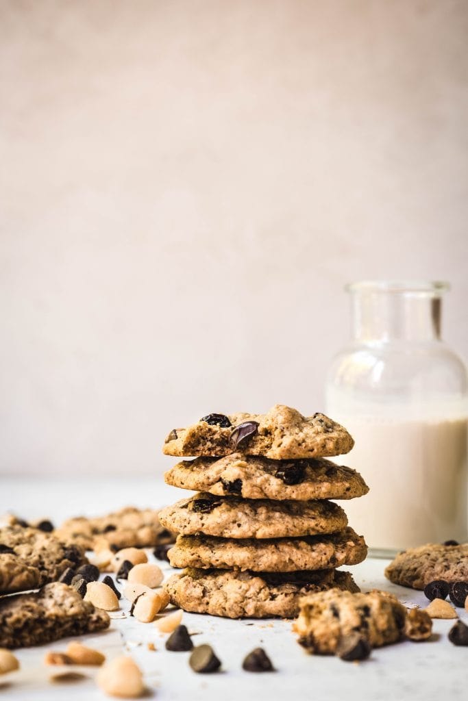 Side view of stack of chocolate chip cherry cookies with macadamia nuts with milk in background