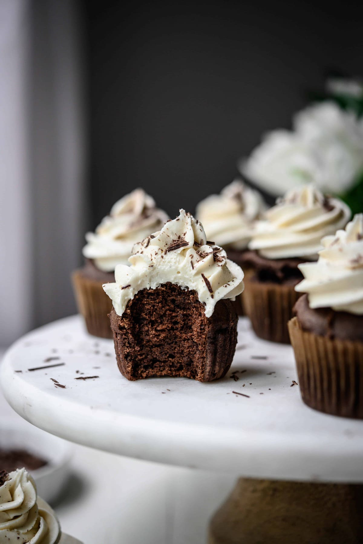 Side view of vegan chocolate cupcakes with vanilla frosting with bite taken out