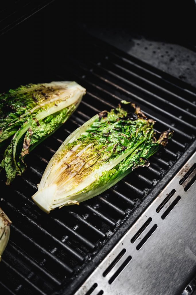 two halves of a head of romaine lettuce on an open grill, with grill marks on the top