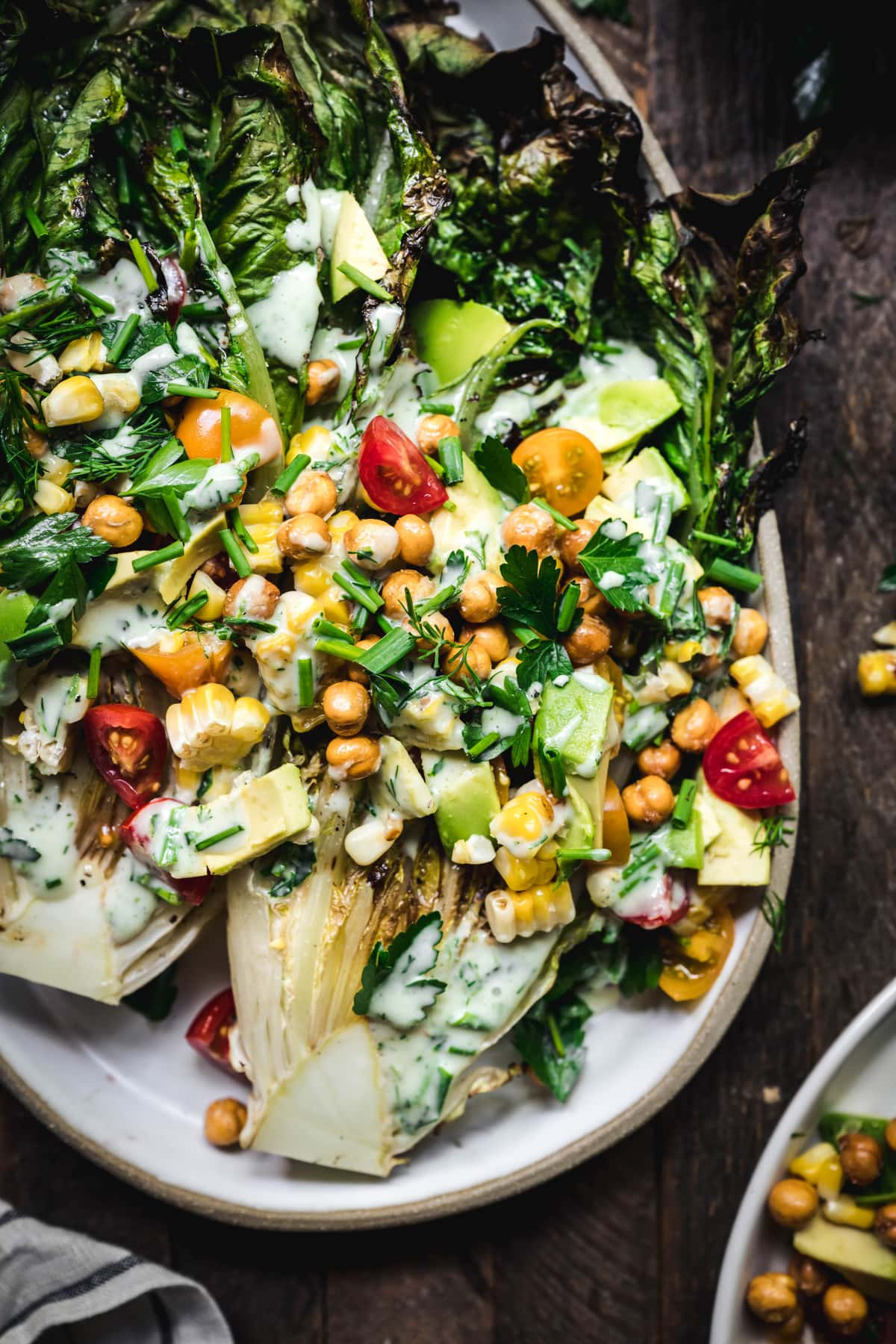 overhead of grilled romaine salad with vegan ranch, crispy chickpeas, grilled corn and avocado