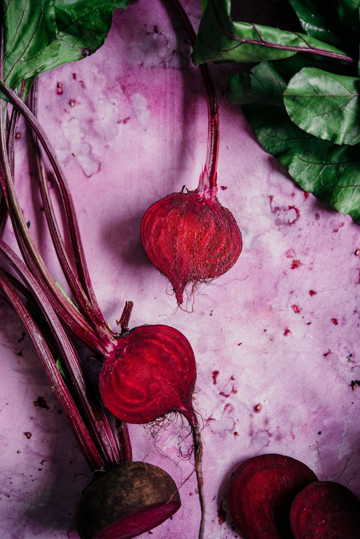 sliced beets on a pink background with beet greens