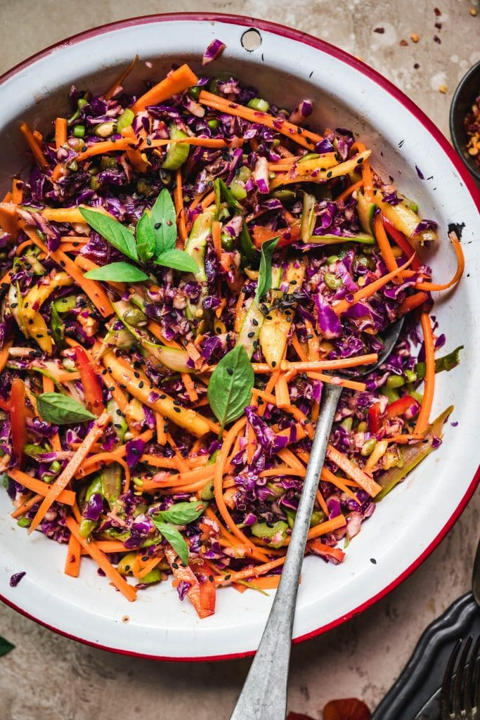 Close up overhead view of rainbow veggie slaw in a white bowl with antique spoon