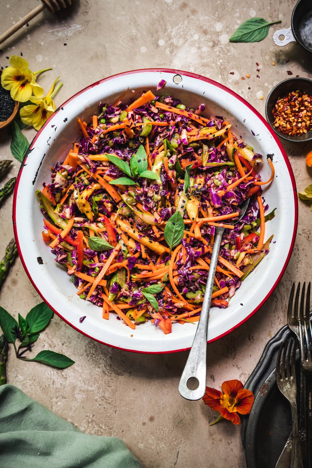 Overhead view of rainbow veggie slaw in a white bowl with antique spoon