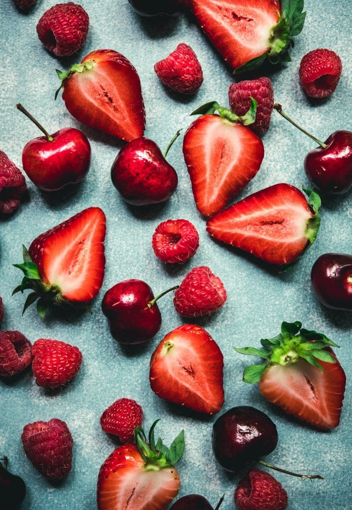 Overhead view of strawberries, raspberries and cherries on blue background