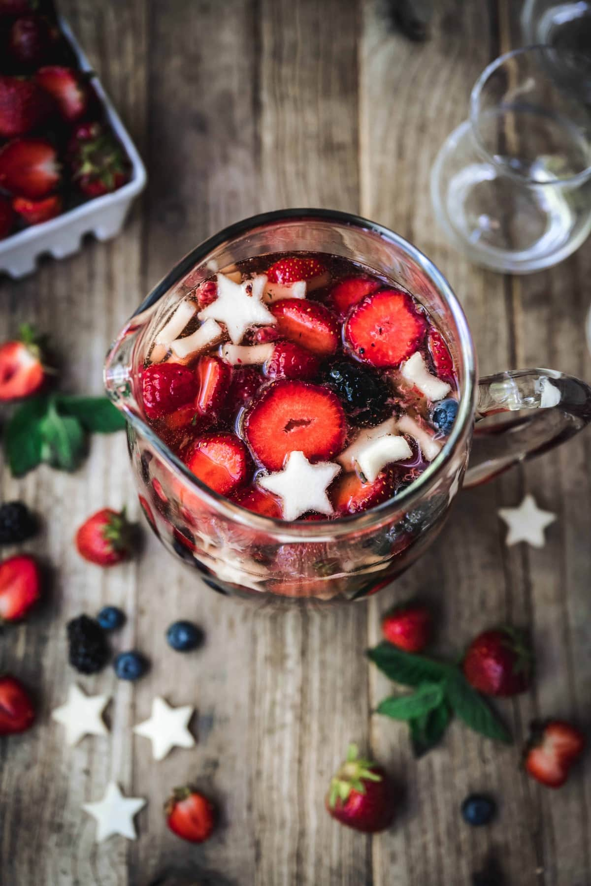 overhead of red white and blue sangria with berries in a pitcher