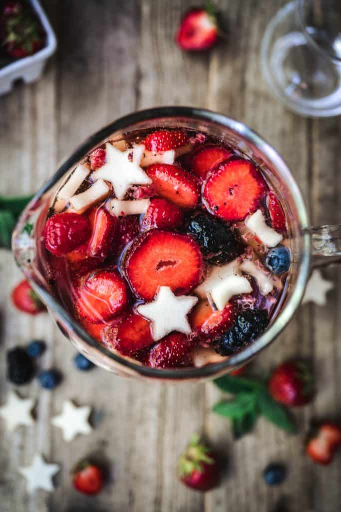 overhead of berries in 4th of july sangria in a glass pitcher