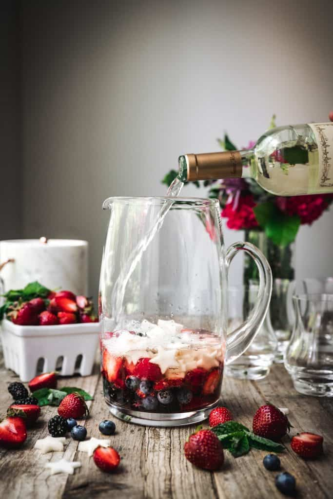 side view of berries to make sangria in a glass pitcher