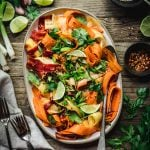 Overhead view of shaved rainbow carrot salad on a platter on rustic wood table