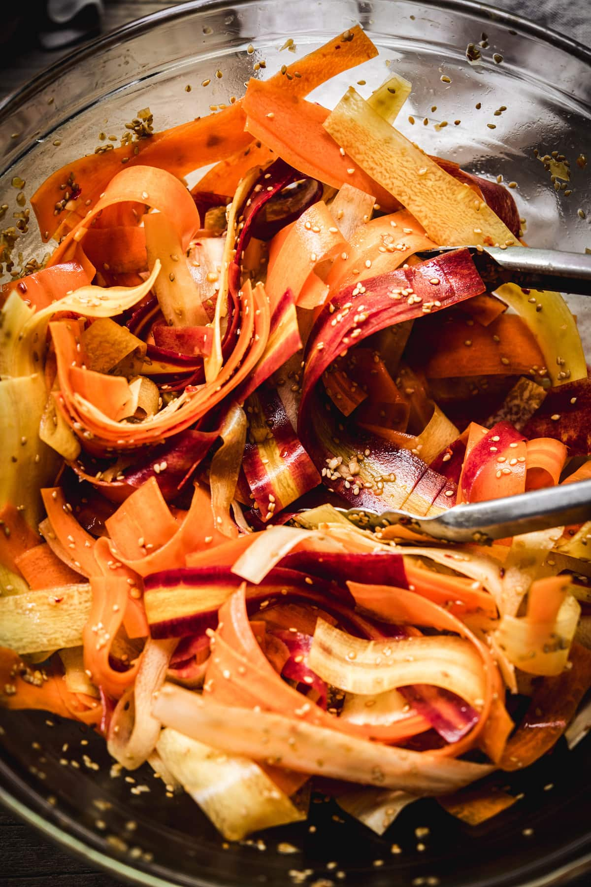 Overhead view of shaved rainbow carrot salad tossed in sesame dressing in glass bowl