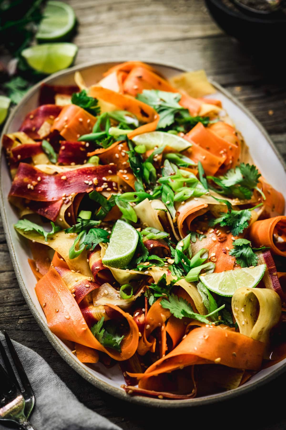 Side view of shaved rainbow carrot salad on a platter on rustic wood table