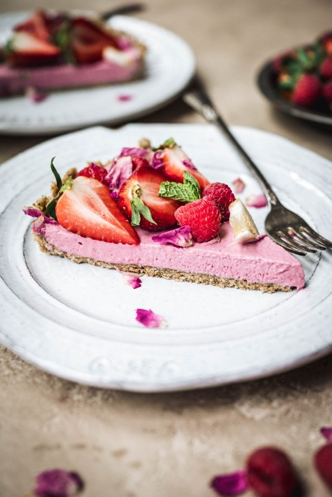 Side view of slice of vegan strawberry mousse pie on a white plate with fork