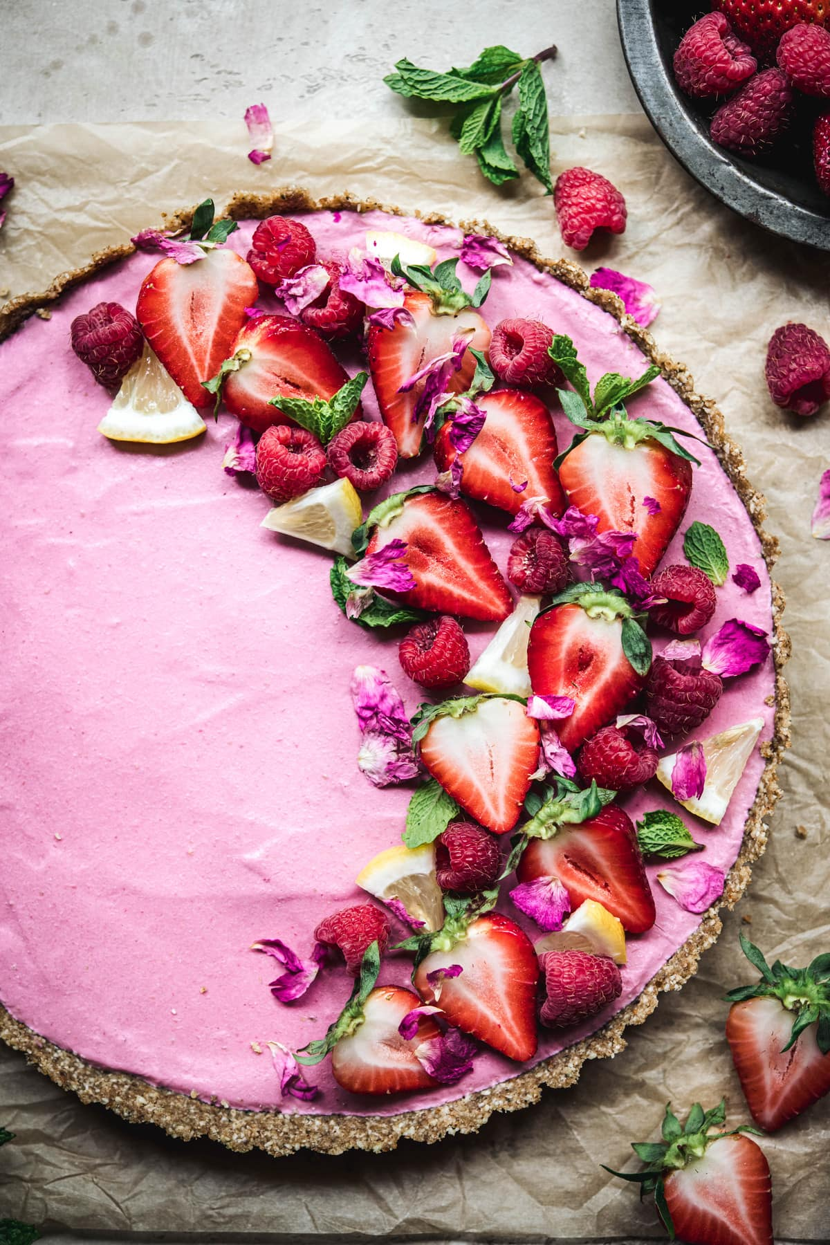 Overhead view of vegan strawberry mousse tart garnished with fresh berries on parchment paper