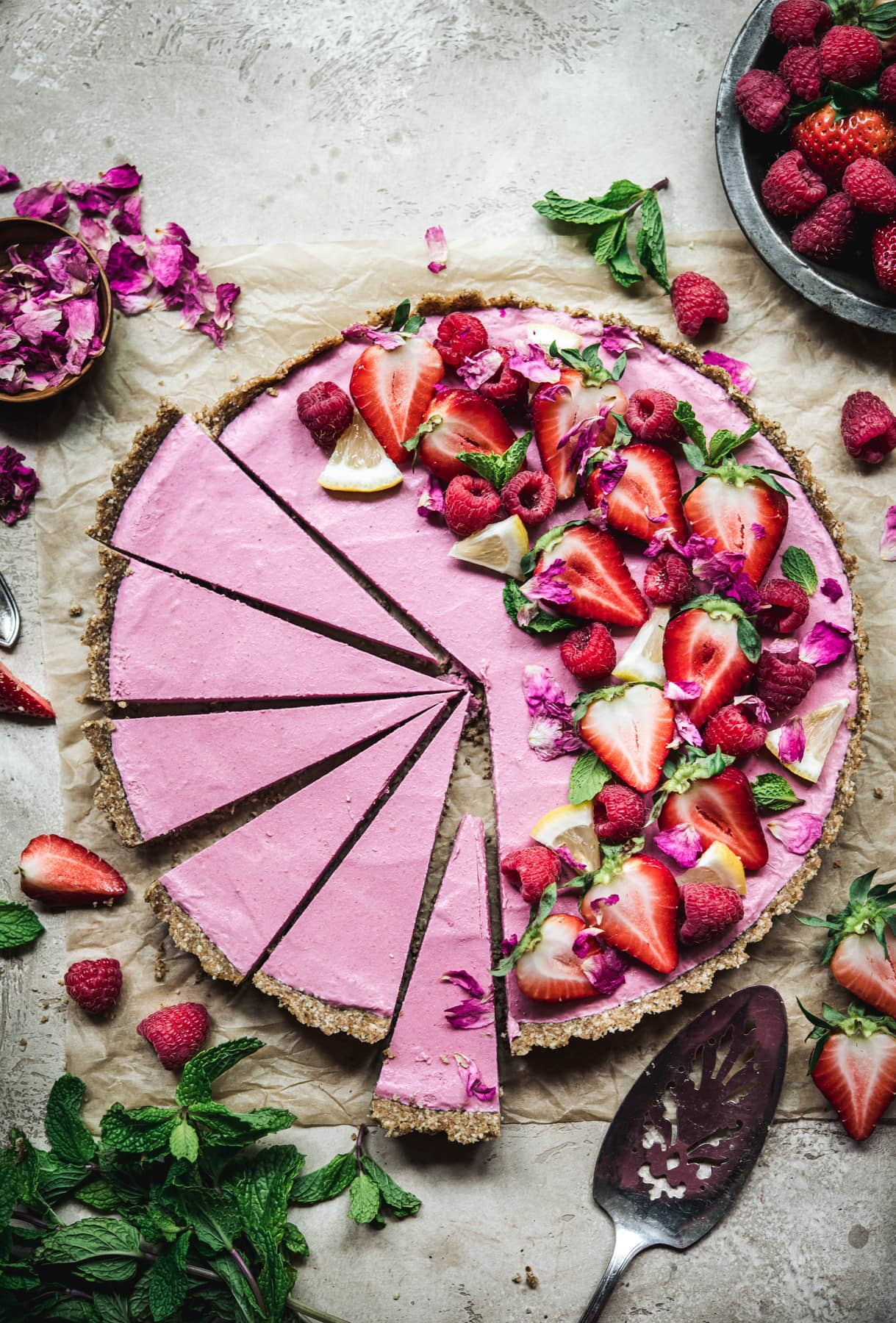 Overhead view of vegan strawberry mousse tart garnished with fresh berries and sliced thinly on parchment paper